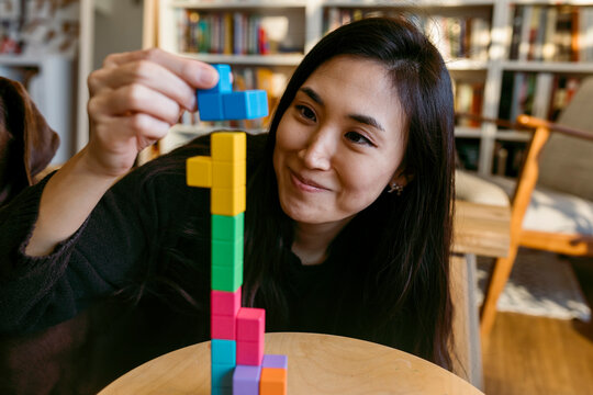female asian woman playing with a wooden puzzle tetris style