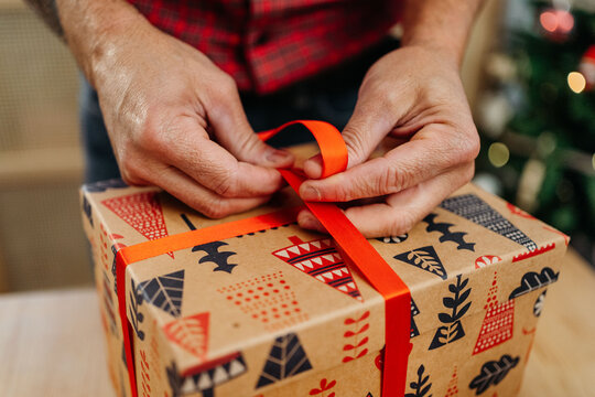 Unrecognizable man wrapping christmas presents
