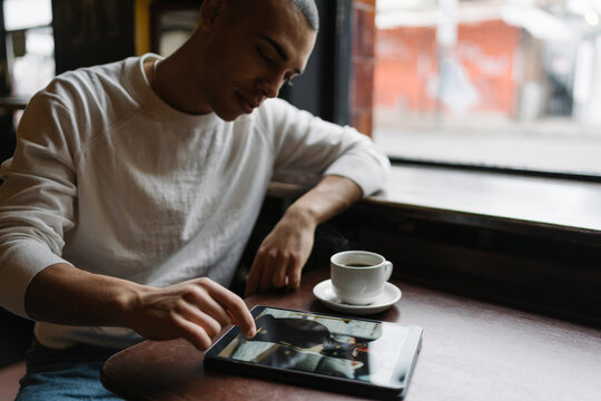 Young Man Using Computer Seated in a Coffee Shop