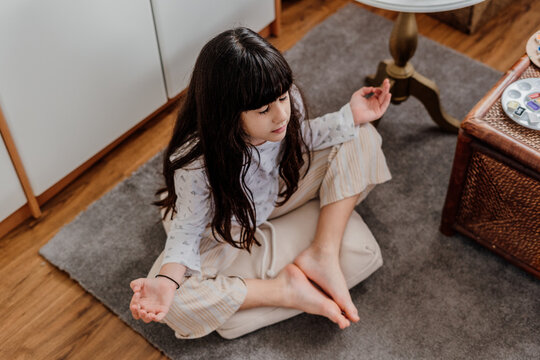 little girl practicing yoga at bedroom