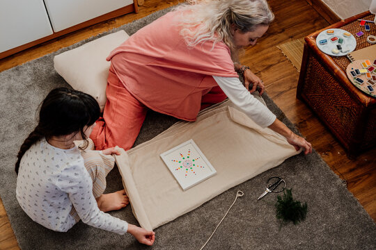 grandmother and grandaughter packing a gift