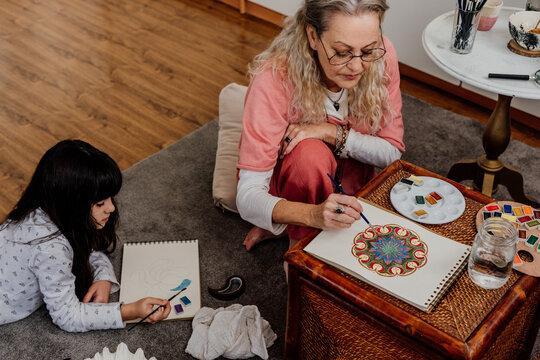 Family painting mandalas at bedroom