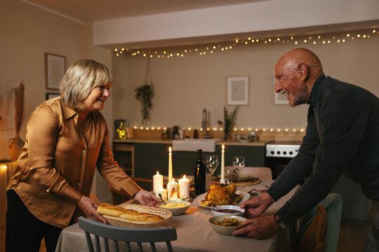 Senior couple setting table for Christmas dinner