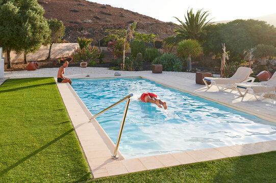Senior men swimming in a pool in summer