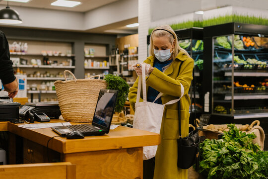 senior woman with protective mask paying at supermarket