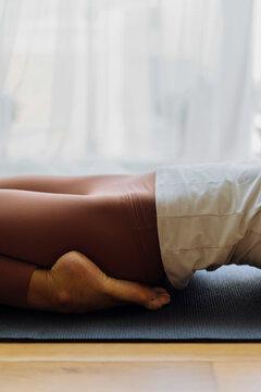 Slim woman lying in yoga position on mat