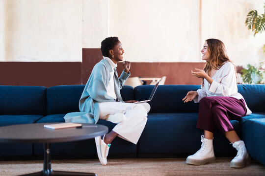 Happy diverse coworkers talking on sofa