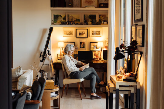 Middle aged woman reading book at home