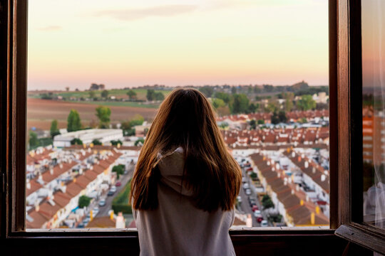 Teenager girl from back looking at city from the window