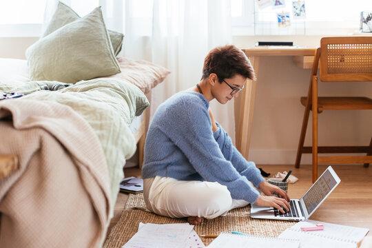 Female teenager using laptop for studies