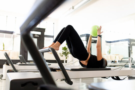 Fit Woman Enjoys Pilates Exercise With Ball