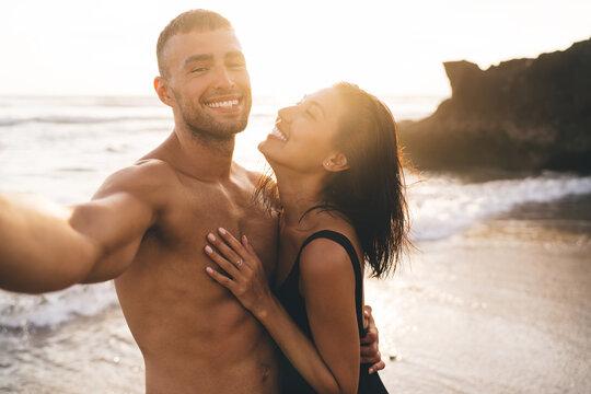 Happy diverse couple embracing on sea coast in sunlight