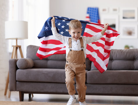 Happy cute little boy holding flag of United States while celebrating independence day of USA with family at home