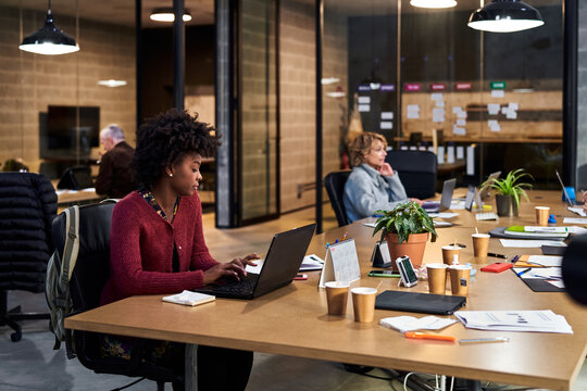 Black woman using laptop near colleagues in office