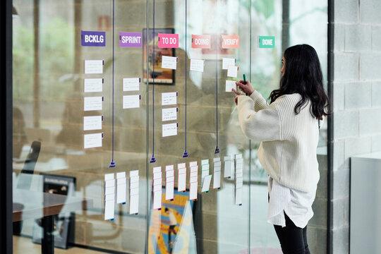 Manager placing tasks on kanban board.