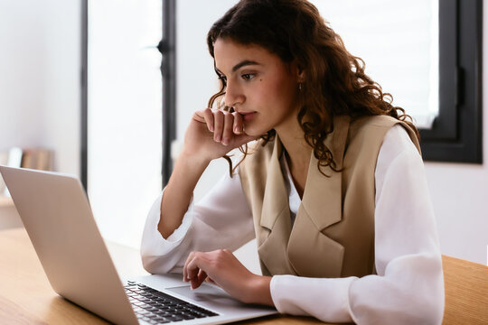 Thoughtful young woman using laptop in workplace