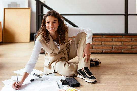 Cheerful woman creating draft on floor