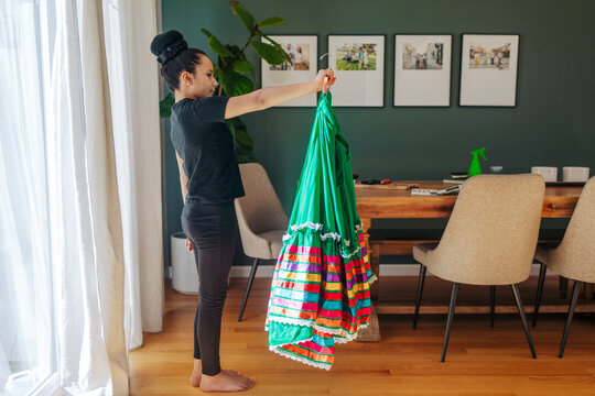 A girl is holding and checking on her green folkloric Mexican skirt