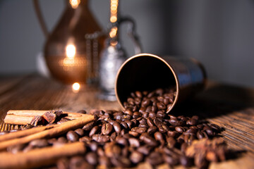 A cup of coffee on a wooden table from old boards. Scattered coffee beans and cinnamon.