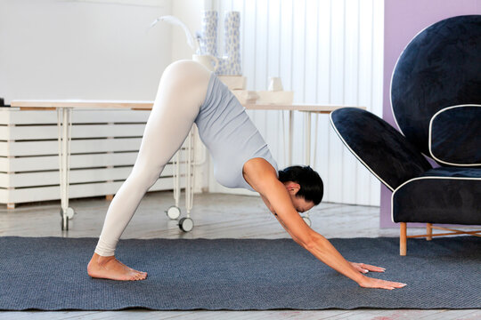 Young sporty woman practicing yoga, working out, wearing sportswear, white pants and grey top