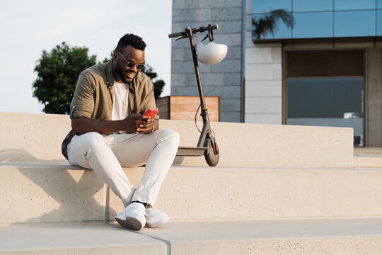 African man using mobile phone having fun with electric scooter outdoor in summer day - Focus on face