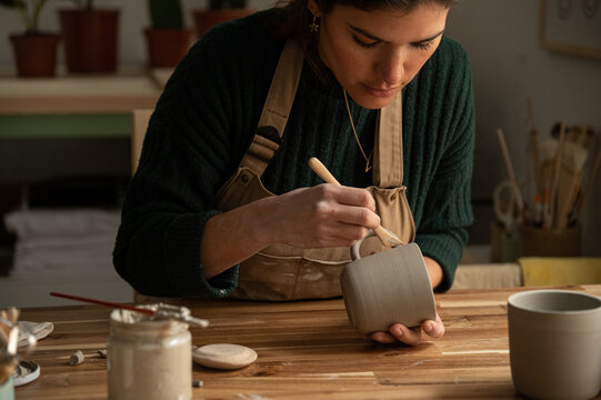 Ceramist young woman Making Clay cups  in her studio