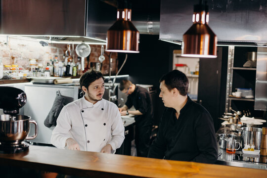 Serious chefs discussing work issues in kitchen