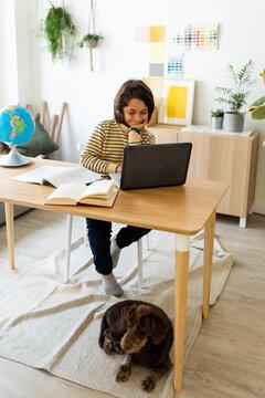 kid sitting on desk using laptop