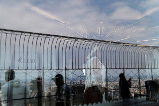People wearing protective face masks are reflected on the observation deck at the Empire State Building in New York City