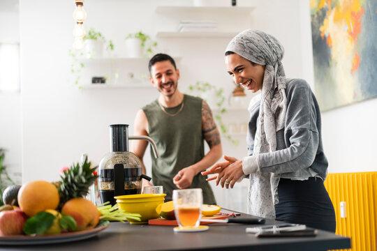 Muslim couple preparing healthy food and talking