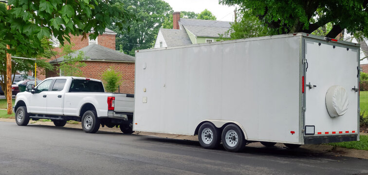White pickup truck and large utility trailer parked on residential city street.