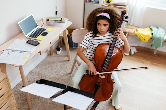 Hispanic girl practicing to play cello at room