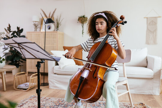 Hispanic cello student during music lesson at home