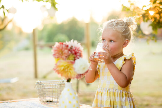 Young girl drinks at outdoor table