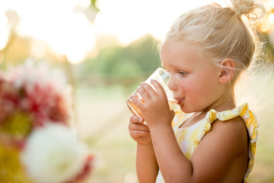 Young girl drinks from glass at outdoor table