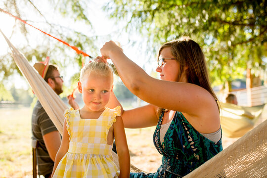 Mother adjusts daughter's ponytail  at campground