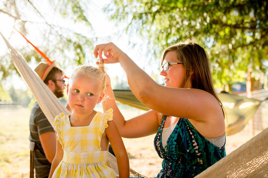Mother fixes daughter's hair at campground