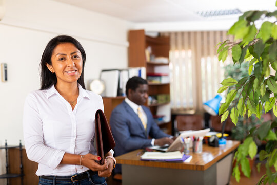 Smiling friendly Hispanic female administrative secretary standing with briefcase of documents in modern office interior.