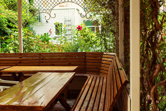 The big alcove with table in patio with flower garden in a guest house. Russia, Black Sea, Krasnodar Region, Anapa