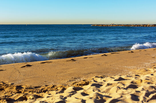 Coastal strip of the Mediterranean Sea with breakwaters and a sandy beach in the San Martí area in Barcelona, Spain
