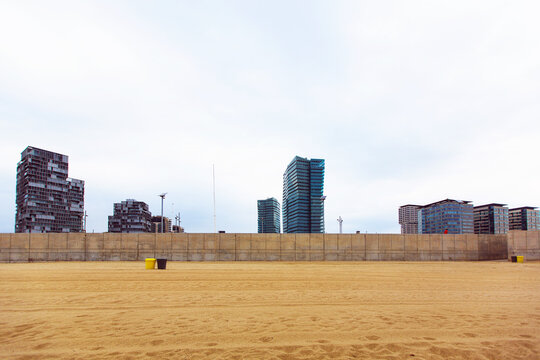 View of multi-storey residential buildings from the coastal strip of the Mediterranean Sea with a sandy beach in the area of San Martí in Barcelona, Spain