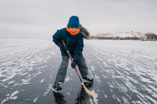 boy playing ice hockey on the frozen river