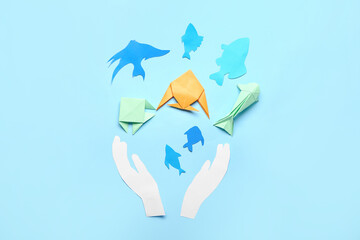 Fototapeta Paper hands with fishes on color background. Ecology concept obraz