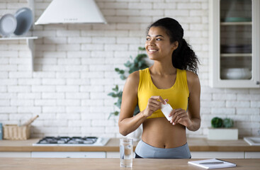 Fototapeta Happy sportive african american woman in sportswear holding a bottle of nutritional supplements, looking happily out the window, healthy lifestyle obraz