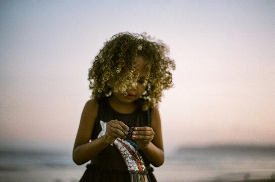 Biracial girl looking at seashell at sunset