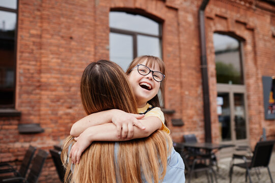 Candid portrait of carefree girl with down syndrome embracing mother outdoors in city, copy space