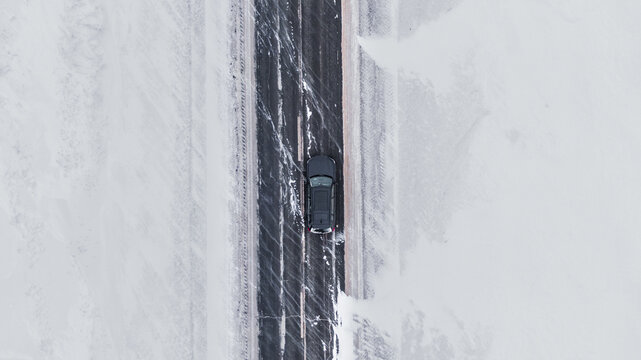 Overhead view Of a brand new black Car on a winter road