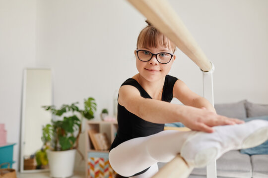 Portrait of cute ballerina with down syndrome standing by bar at home and doing stretching exercise, copy space