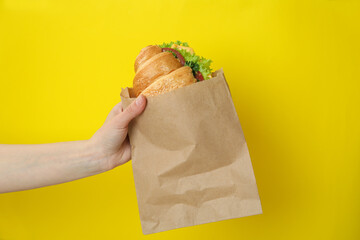 Female hand hold croissant sandwich on yellow background