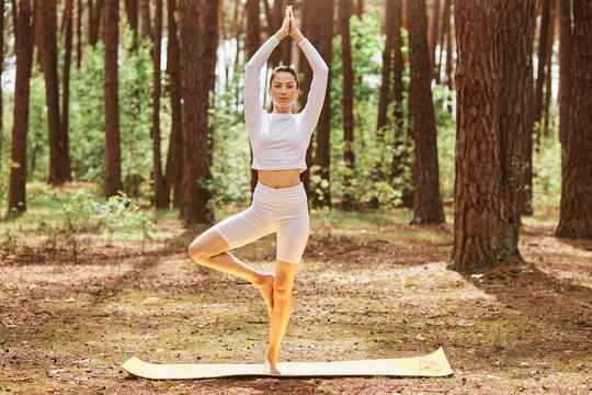 Full length portrait of attractive female wearing sportswear standing on karemat in yoga pose on one leg, raising hands up, practicing yoga in forest.